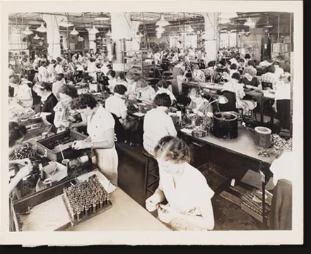 Skilled fingers deftly assemble the thousands of small parts for Philco radios.