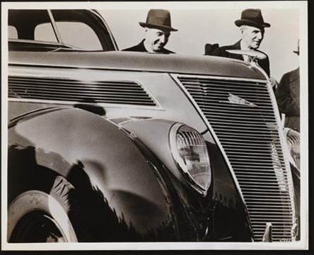 This unusual camera shot shows Henry Ford (right) and Edsel Ford with their newest product, the Ford V-8 for 1937. The picture was taken at Dearborn during the newspapermen's preview of the new car, which excited unusual interest because of its completely new appearance and the advent of the 60 horsepower V-8 engine, giving a choice of engine sizes.