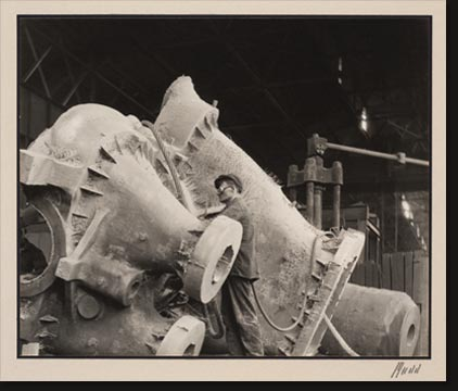 Workmen with pneumatic chipping hammers clean a steel casting. The casting is a turbine casing and weighs 51,000 pounds.