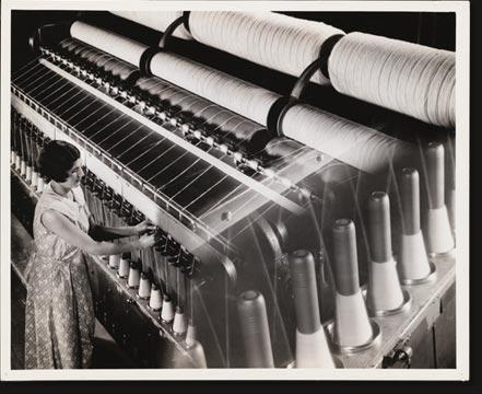 A newer machine for spinning is the frame shown here. The principle is the same as in mule spinning, but the draw is continuous. Running between the two sets of rollers, one of which turns faster than the other, the roving is drawn down to size, while the spindle revolves, twisting the yarn and winding it in the same operation.